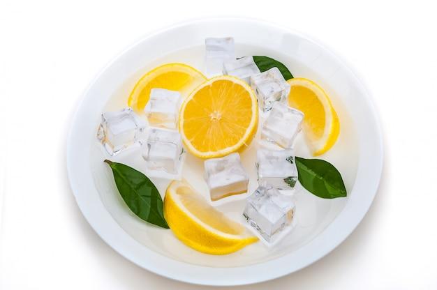 Lóbulos de limão fresco, suculento, brilhante, amarelo, cubos de gelo refrescante e folhas verdes em uma placa em um fundo branco