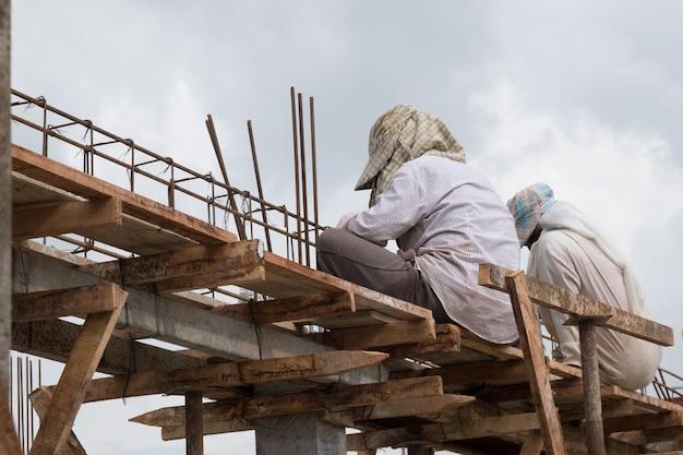 Local de construção com costas de dois trabalhadores