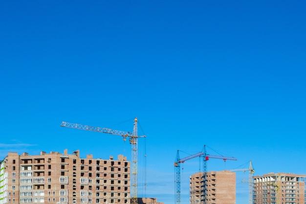 Local de construção. prédios de vários andares em construção. guindastes de torre perto de edifícios.