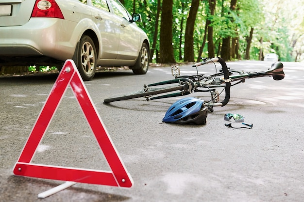 Local de desastre. bicicleta e acidente de carro prateado na estrada na floresta durante o dia