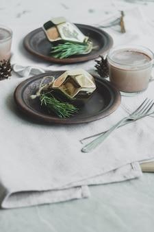 Local de jantar decorado com pinhas, galhos e decorações douradas de natal