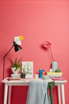 Local de trabalho aconchegante com coisas diferentes. lindas calla liles em um vaso, pilha de livros, diário aberto com notas escritas