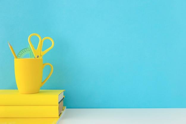Local de trabalho azul para estudantes com acessórios amarelos
