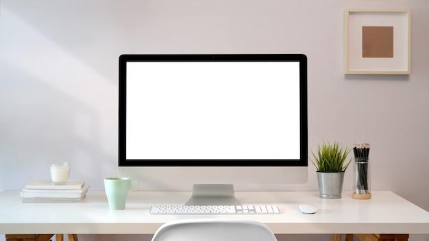 Local de trabalho com a tabela de trabalho confortável do pc da tela em branco. espaço de mesa sotão
