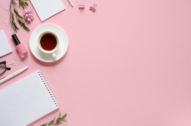 Local de trabalho com bloco de notas, caneta, xícara de café e outros acessórios em fundo rosa com espaço de cópia. vista do topo
