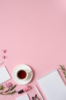Local de trabalho com bloco de notas, caneta, xícara de café e outros acessórios em fundo rosa com espaço de cópia