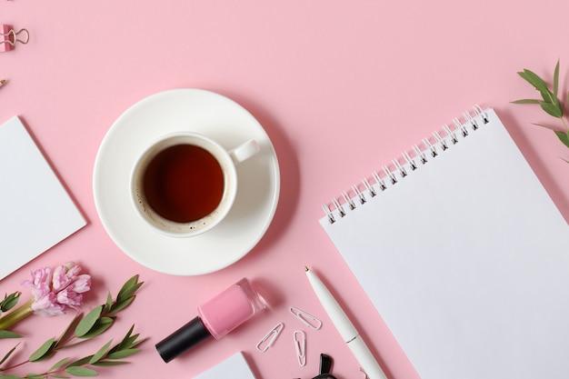 Local de trabalho com bloco de notas, caneta, xícara de café e outros acessórios na mesa rosa. vista do topo