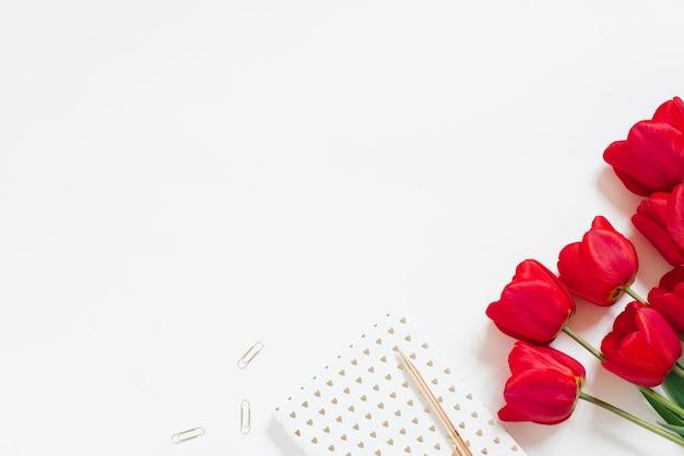 Local de trabalho com bloco de notas, tulipas vermelhas, caneta, clipes de papel em um fundo branco. cama plana, vista superior