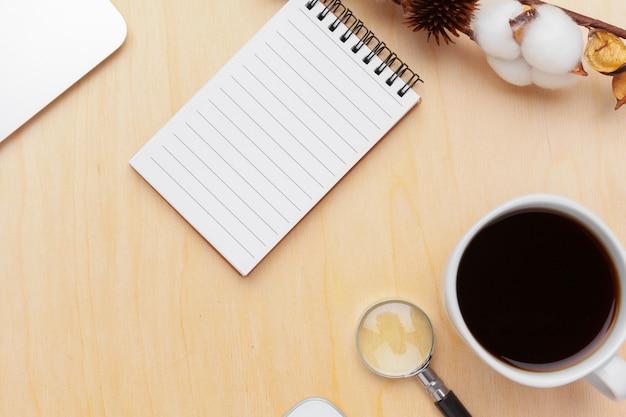 Local de trabalho com café, caderno espiral e lupa