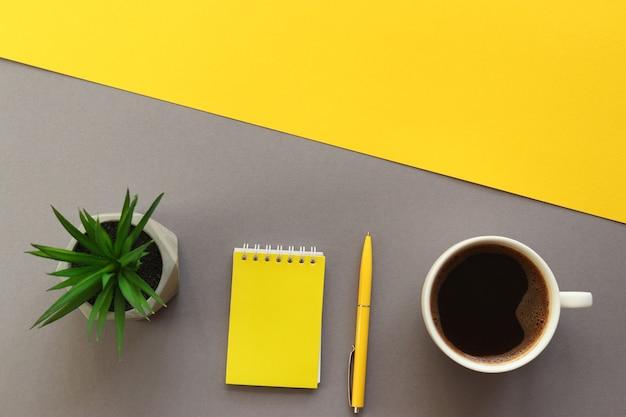 Local de trabalho com caneta de bloco de notas, xícara de café e planta suculenta na mesa de escritório amarela e cinza da moda
