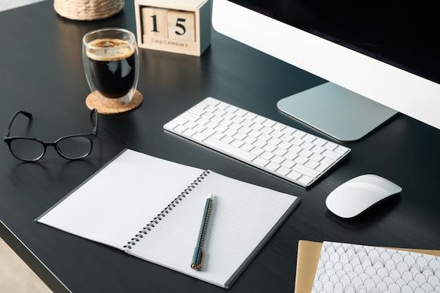 Local de trabalho com computador, copo de café e caderno vazio na madeira, closeup