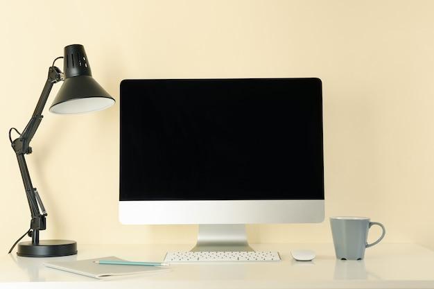 Local de trabalho com computador desktop contra fundo bege