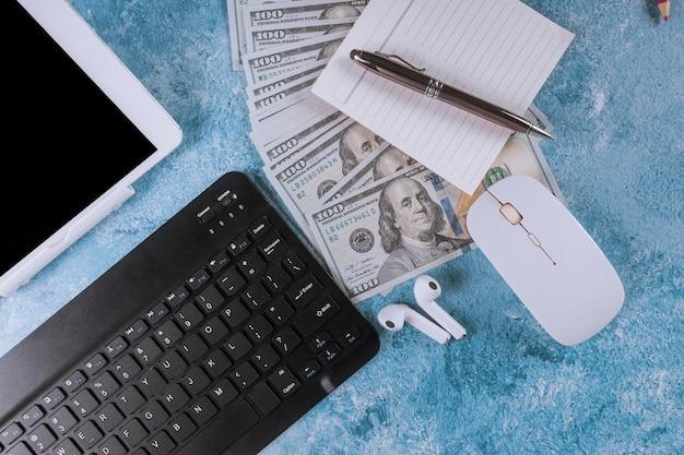 Local de trabalho com computador e dólares em dinheiro.