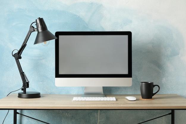 Local de trabalho com computador, lâmpada e café na mesa de madeira. luz de fundo azul