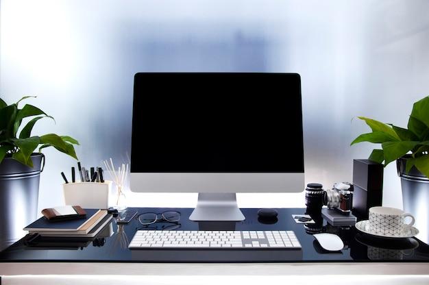 Local de trabalho com computador moderno na mesa de vidro, mock up tela preta, planta de casa e suprimentos.