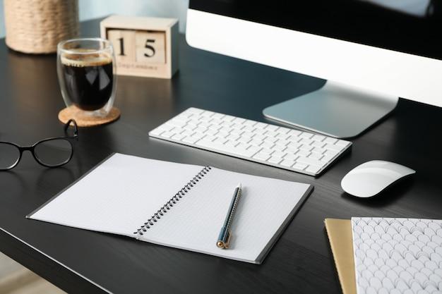 Local de trabalho com computador, óculos e calendário na mesa de madeira preta, close-up