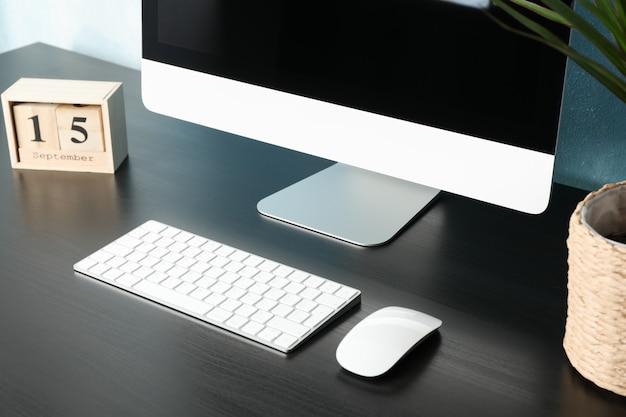 Local de trabalho com computador, planta e calendário na mesa de madeira preta, close-up