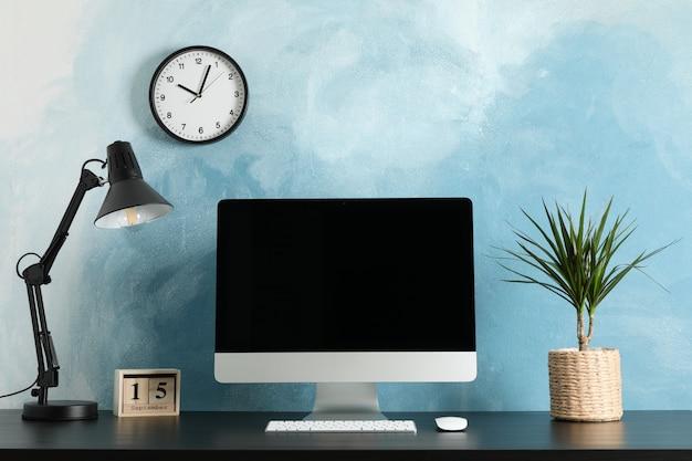 Local de trabalho com computador, planta e lâmpada na mesa de madeira. luz de fundo azul