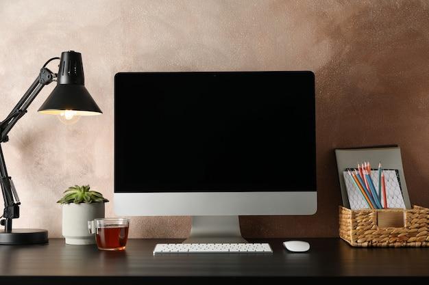Local de trabalho com computador, planta e lâmpada na mesa de madeira.