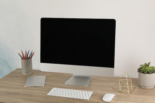 Local de trabalho com computador, planta e tablet na mesa de madeira. tela preta vazia