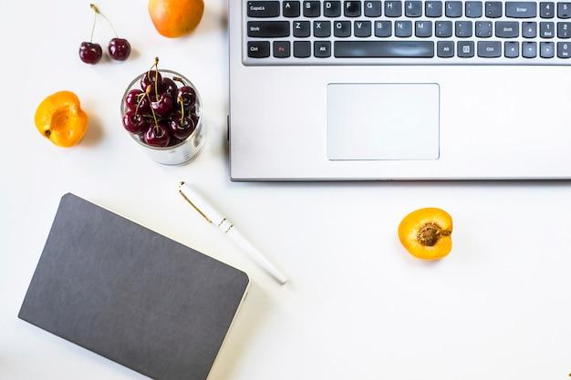 Local de trabalho com computador portátil e o bloco de notas na mesa branca com frutas e frutas lanche
