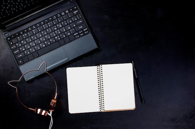 Local de trabalho com computador portátil, smartphone, caneta, bloco de notas