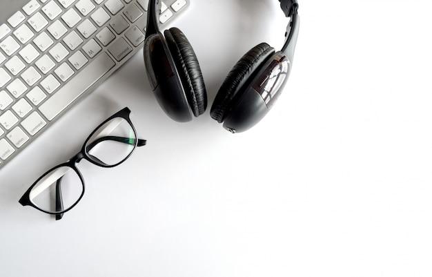 Local de trabalho com espaço de texto, computador de teclado e fones de ouvido na mesa de wthte. sobre a luz