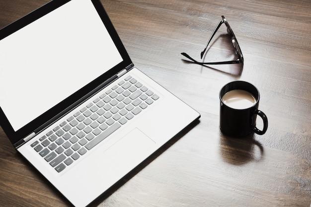 Local de trabalho com laptop aberto, café e acessório na mesa de escritório.