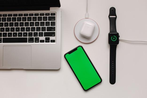 Local de trabalho com laptop na mesa e dispositivos. carregamento sem fio do relógio inteligente e fones de ouvido sem fio na mesa branca. smartphone com tela verde, mock up. vista do topo.