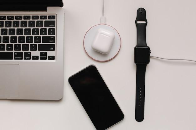 Local de trabalho com laptop na mesa e dispositivos. carregamento sem fio do relógio inteligente e fones de ouvido sem fio na mesa branca. vista do topo.