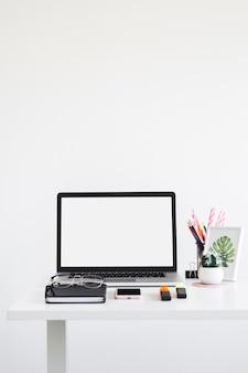 Local de trabalho, com, laptop, perto, óculos, caderno, marcadores, e, telefone móvel