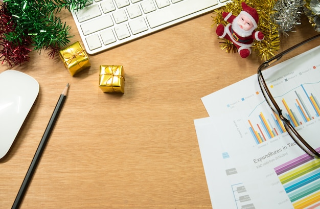 Local de trabalho com laptop, presentes de natal, caneta, caderno na mesa.