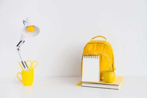 Local de trabalho com mochila amarela e apple