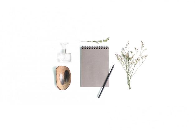 Local de trabalho com notebook, flores e acessórios femininos, vista plana, vista superior