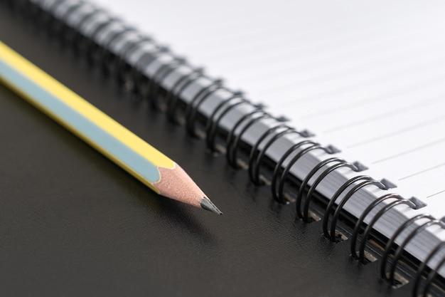 Local de trabalho com o bloco de notas e lápis, lápis e caderno para o fundo do negócio.
