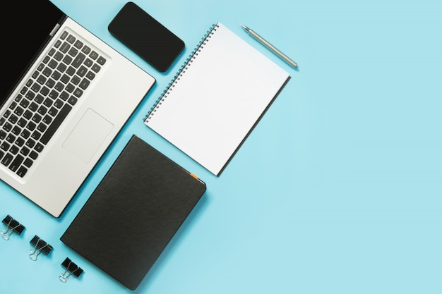 Local de trabalho com o laptop aberto, acessório branco e preto na mesa azul.