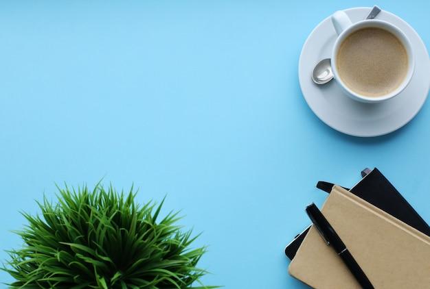Local de trabalho com planta, cadernos e xícara de café