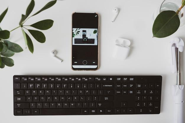 Local de trabalho com smartphone teclado e fone de ouvido em fundo branco