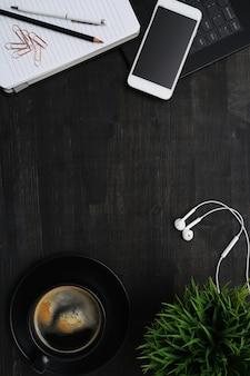 Local de trabalho com smartphone, xícara de café, caderno, mesa preta. vista superior fundo