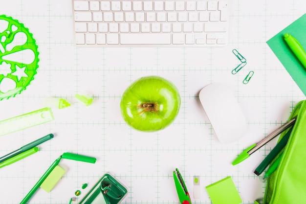 Local de trabalho com teclado, apple e papelaria