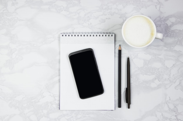 Local de trabalho com telefone, bloco de notas, caneta de escrever e uma xícara de café em uma mesa de mármore. vista superior, configuração plana, cópia espaço
