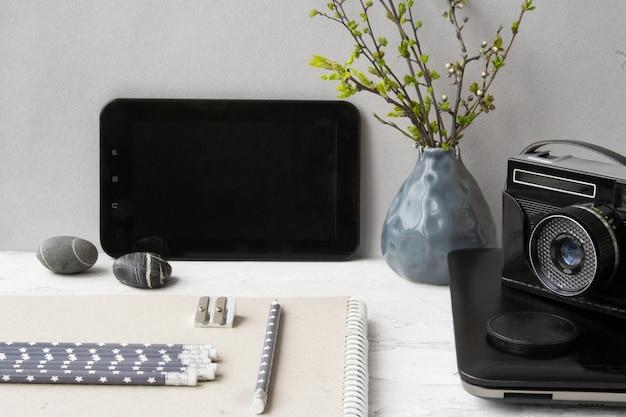 Local de trabalho com um laptop, notebook e câmera retro. trabalho em casa