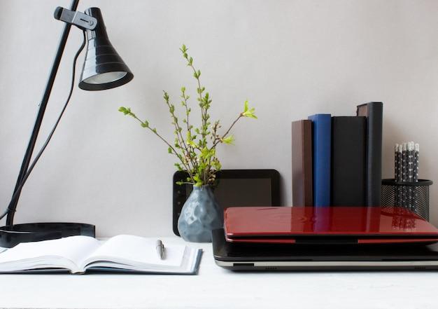 Local de trabalho com um laptop, notebook e lâmpada. trabalhe em casa em quarentena e isolamento