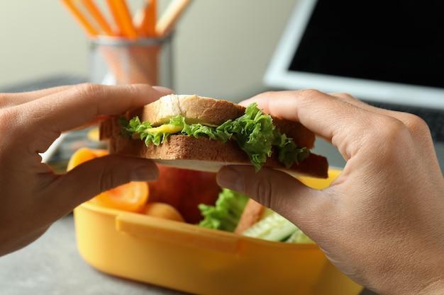 Local de trabalho comendo com mãos femininas segurando sanduíche, close-up