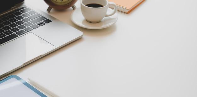 Local de trabalho confortável com computador portátil, xícara de café e material de escritório na mesa de madeira branca