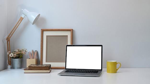 Local de trabalho confortável com laptop de tela em branco, notebooks, xícara de café e maconha na mesa branca.