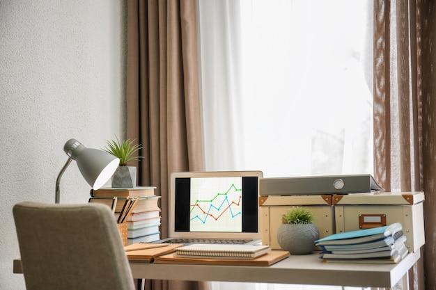 Local de trabalho confortável com laptop na mesa em casa