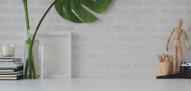 Local de trabalho confortável com moldura e material de escritório na mesa branca
