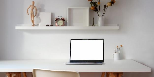 Local de trabalho confortável com o computador portátil de tela em branco na mesa de madeira branca