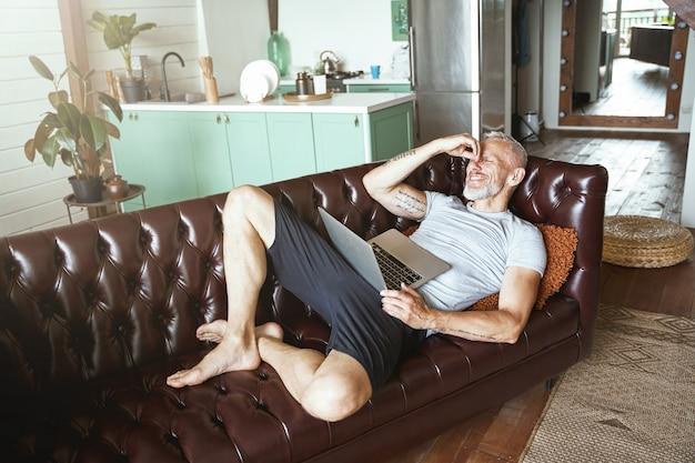 Local de trabalho confortável, feliz, homem caucasiano de meia-idade, vestindo roupas casuais, usando laptop enquanto